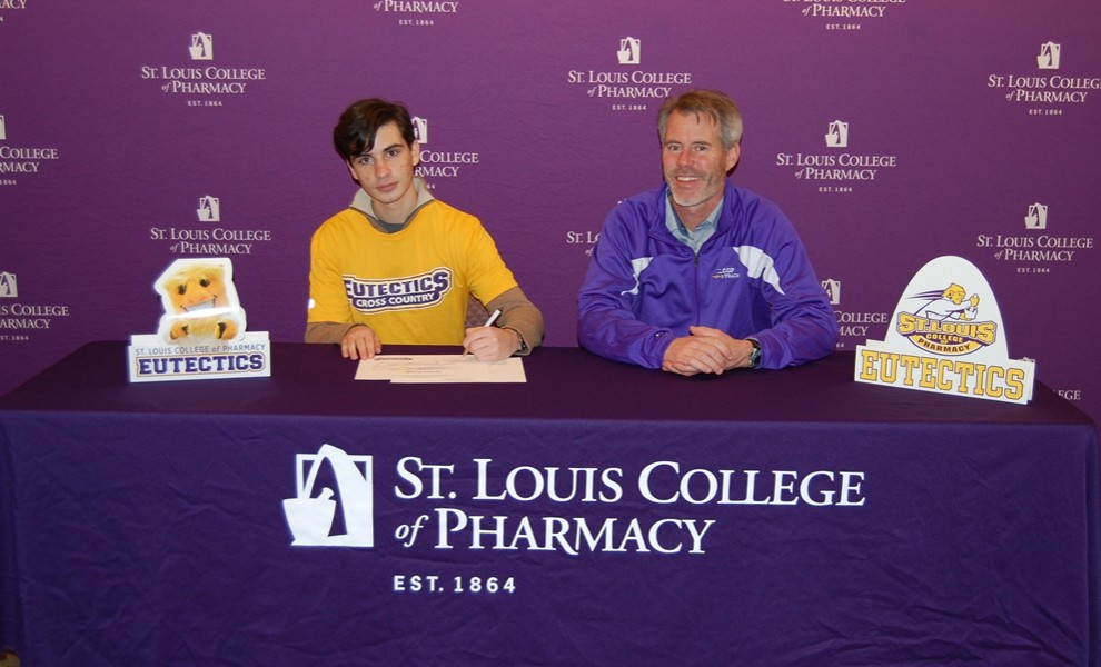 Matthew Ruvinov, with head coach David Baker, signs a letter of intent to run cross country and track at STLCOP.