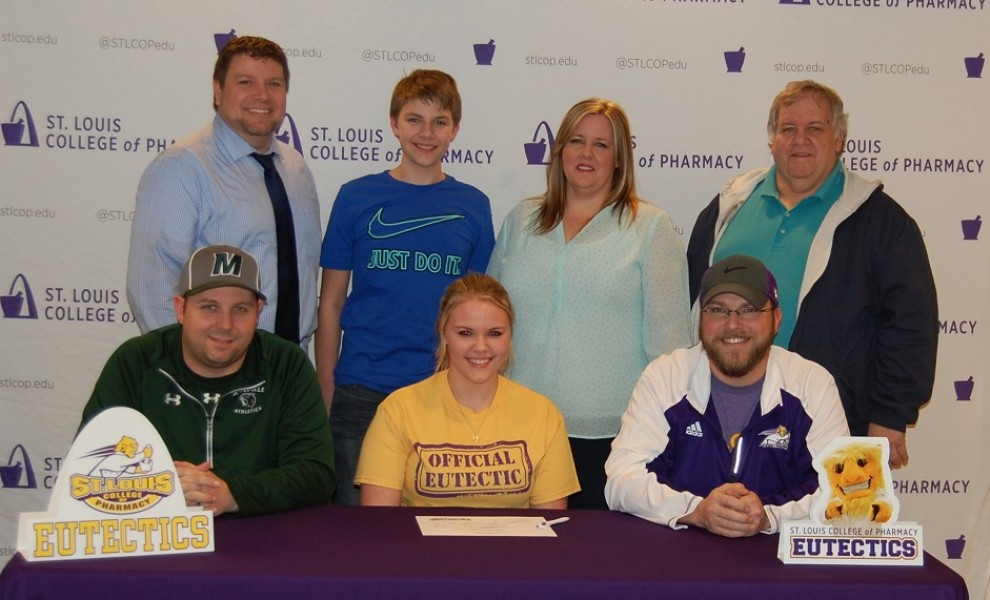 Mackenzie White is flanked by her MHS coach and STLCOP coach, while her family stands behind her as she signs her LOI.